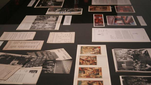 A close-up of one of the tables reveals photographs and documents that reflect the history of The New School's art collection and that of the university itself.