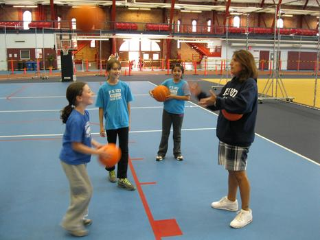 Gym teacher Diane DiTonne-Gihuley and kids playing basketball