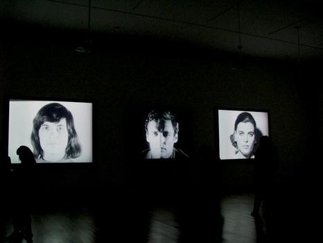 An installation view of Warhol's Screen Tests at MoMA, featuring (from left to right): Susan Sontag, Dennis Hopper and Kathe Dees. Sontag doesn't break; Hopper is a ham.