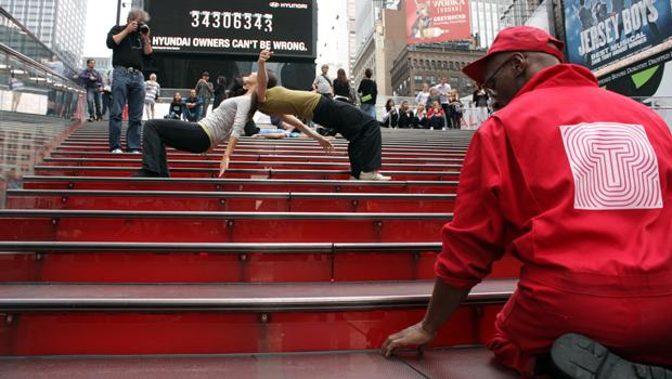 Onlookers watch the Shen Wei Dance Arts dancers on the Duffy Square steps