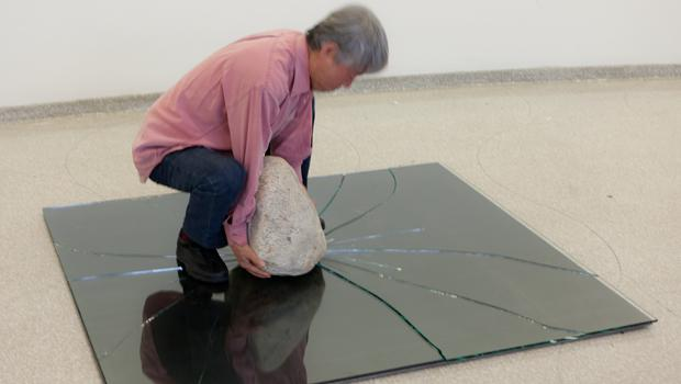 "Ufan breaking the glass for ""Relatum"" (formerly ""Phenomena"" and ""Perception B""), 1968/2011, while installing his show."