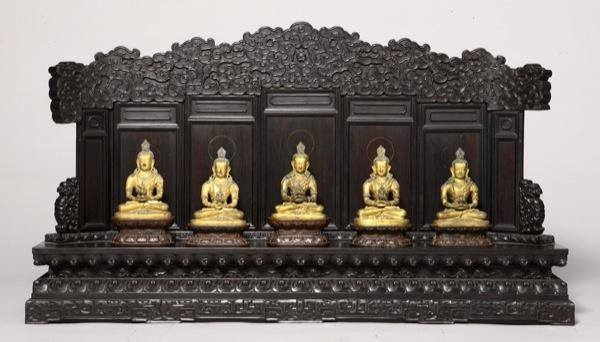 At the Met: Treasures from the private Forbidden City retreat of an 18th century Chinese monarch. In this image, a row of statues of Amitabha on a purple sandalwood stand.