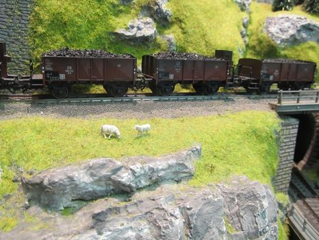 Tiny sheep graze near a model freight train.