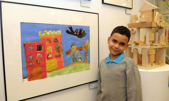 Second-grader Jadiel Espinal stands alongside his piece. He's a student at P.S. 46 in Manhattan.