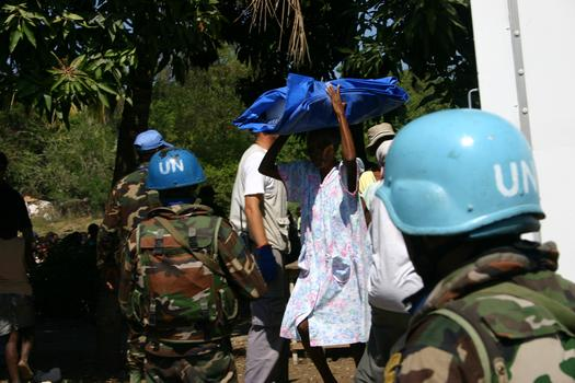 UN troops provide security as an NGO distributes shelter materials
