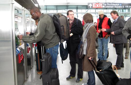 Passengers purchase AirTrain tickets.