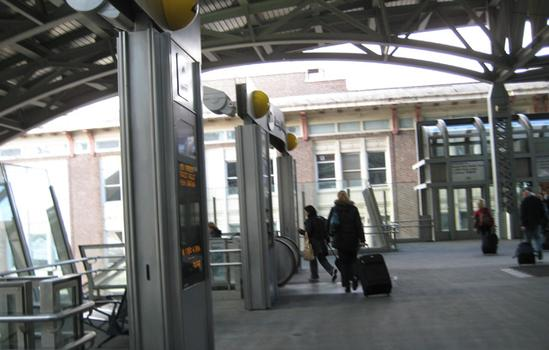 Passengers at Jamaica carry luggage down stairs.