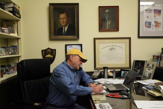 Alan Adler in his office at Streit's Matzos, surrounded by portraits of family members.