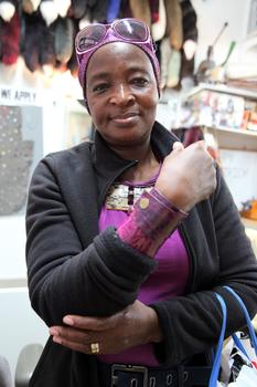 Ami Nata, an immigrant from Burkina Faso, purchases snaps for the bracelets she sells.