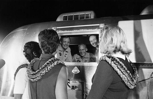 Astronauts, still in their quarantine van, greet their wives. (NASA)
