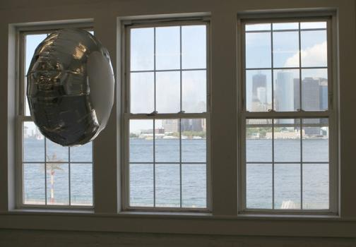 A wistful balloon awaits the truth by the gallery window, with the skyline of Lower Manhattan in the distance.