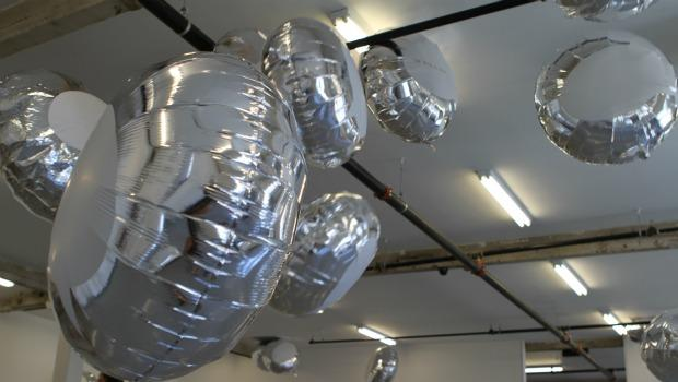 With the aid of several whooshing fans, the balloons whirl through the gallery.