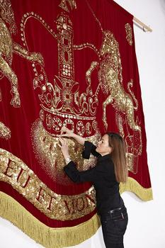 Ann Carrington working on the banner for the Royal Barge.