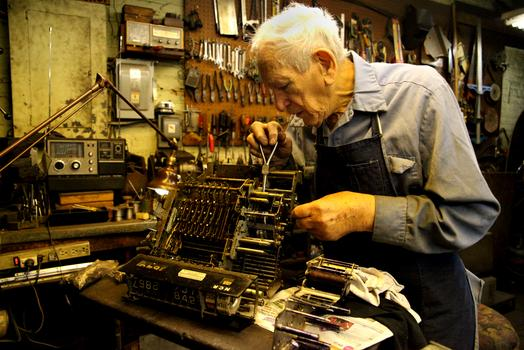 Bernard Faerman repairing a cash register.