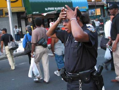 A police officer directs pedestrians and traffic at 14th Street and Sixth Avenue.