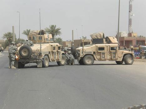 In this shot, Wilkens' squad fixes a broken down humvee in Baghdad.