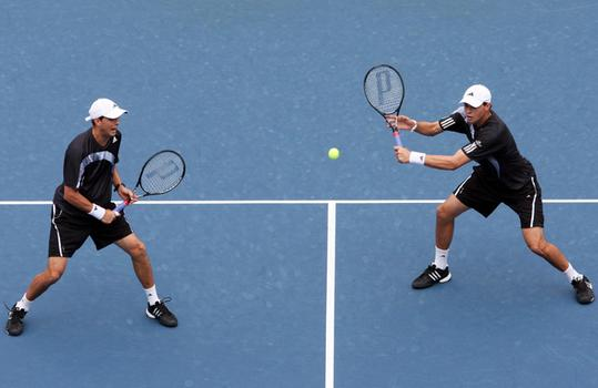 Bob Bryan (R) and Mike Bryan return a shot.