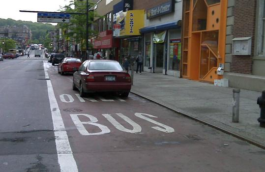 """Cars parked in \""""Select Bus Lane\""""."""