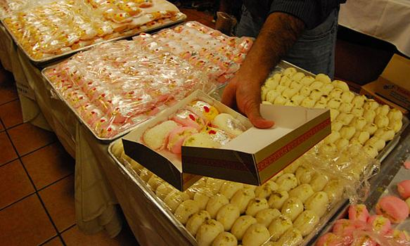 A mixed box of chandrakala, which contain almonds, powdered sugar, cardamum and saffron, among other ingredients.
