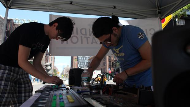 "Two group of ""circuit benders,"" Sean Mcintyre, (L) 24, who took the day off from his job in finance, and Vector Zero (R) playing re-purposed toy keyboards using solar power."