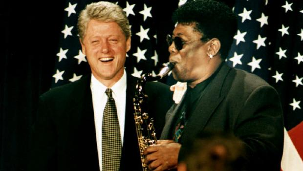 "Former president Bill Clinton laughs as Clarence Clemons plays a rendition of the presidential tune ""Hail to the Chief"" at a fundraiser in 1993."