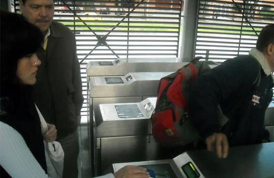 Passengers pass fare cards over an automated machine to speed entry.