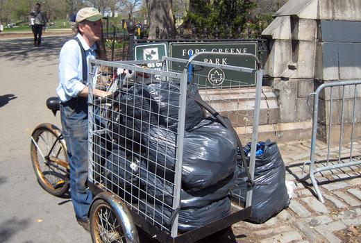 A volunteer hauls bags of collected food scraps to community gardens.