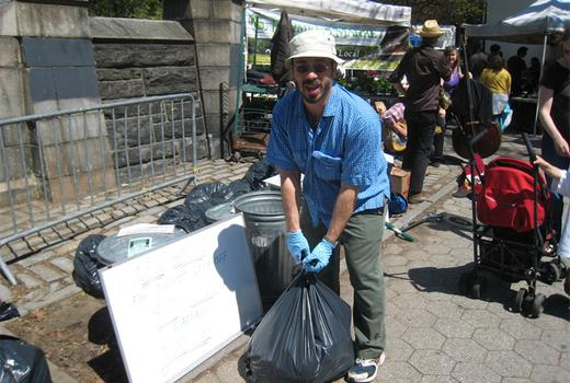 A community garden volunteer bags up food scraps for composting.