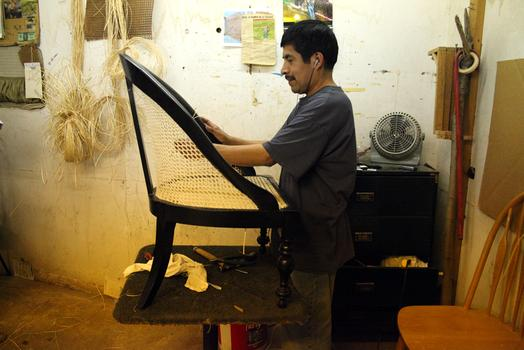 Diego Maldonado, who has been working at Veteran's for 12 years, hand caning a chair.