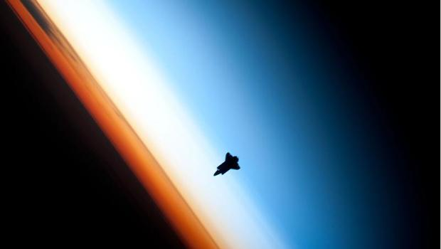 Earth's horizon and the silhouette of the space shuttle Endeavour taken by members on board the International Space Station.