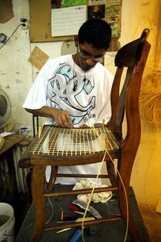 Eric Aguilar canes a chair.