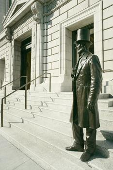 A bronze statue of Abraham Lincoln. The 77th Street entrance  has improved accessibility for school groups and visitors with disabilities, and illumination to highlight the features at night.