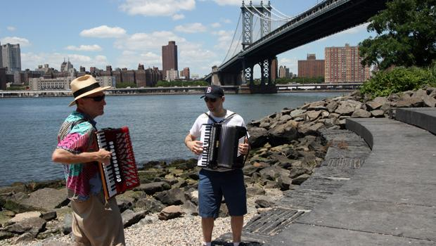 "Bob Goldberg and Carl Riehl of ""The Famous Accordian Orchestra""  play on the pebble beach near the Brooklyn Bridge."