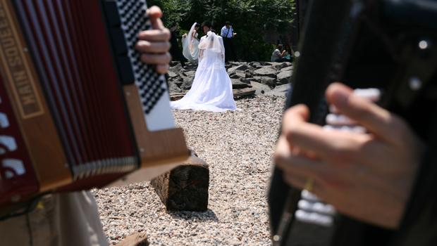 A wedding party receives a suprise accordian-serenade as they pose for photos under the Brooklyn Bridge.