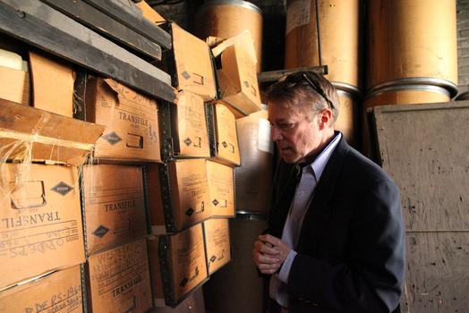 Gregg Monsees standing next to boxes of files from 1950 era orders.