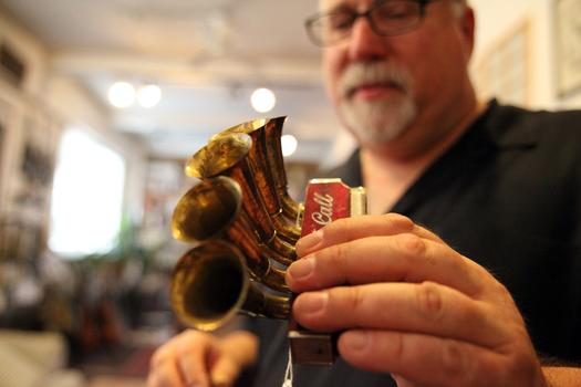 Steve Uhrik holds a harmonica with ornamental horns.