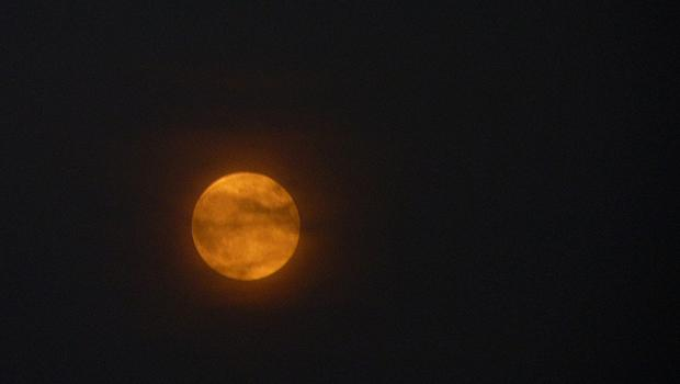 A full moon rose opposite the setting sun on this year's autumn equinox, something that has not happened since 1991. Unfortunately the evening was very hazy, so the moon is partially obscured.