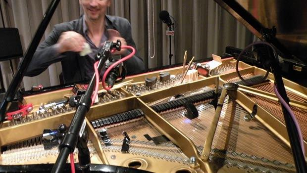 Hauschka's hands and long view of piano insides, including chopsticks, tamborines, ebows, necklace chains, vibrators and tape.
