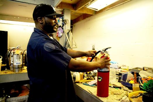 Henry Bryant recharging an extinguisher.