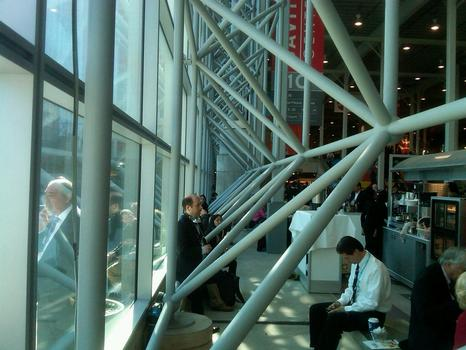 Convention goers sitting by the windows of the center.
