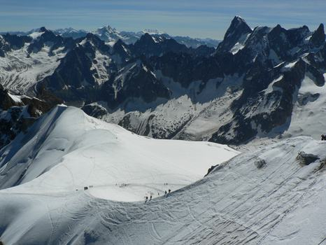 From the Aiguille du Midi, a mountain peak above Chamonix, ice climbers walk out on a vast snowfield.