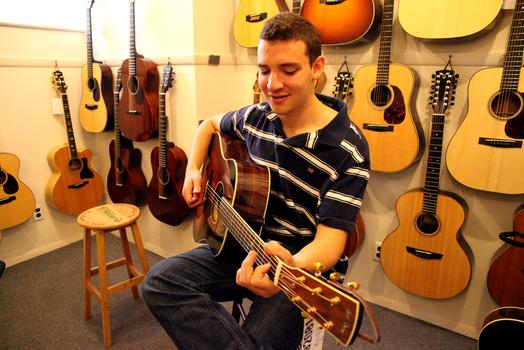 Joe Fox trying out a guitar at Mandolin Brothers.