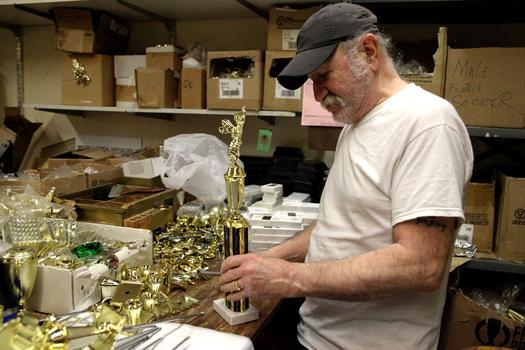 Assembling trophies at Trophy World.