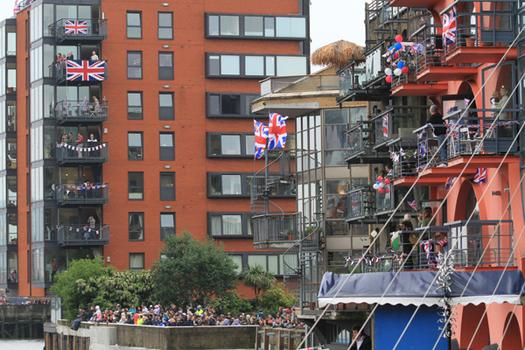 People stood on balconies along the river, waiting for the Queen's barge to arrive.