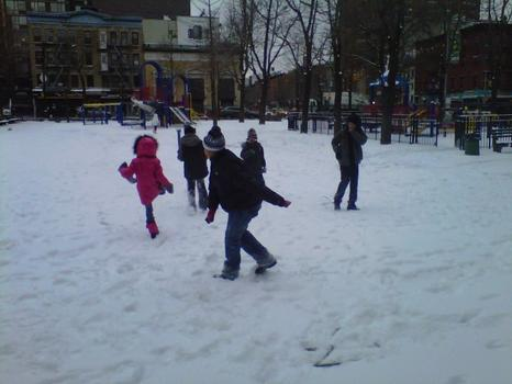 Kids have fun in the snow at a Lower East Side park.