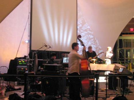 "<strong>John Schaefer (far R) introduces ""Eclipse"", featuring the Bill Frisell trio; percussionist Kenny Wollesen, double bass player Tony Scherr, guitarist Bill Frisell, 1/15/04.</strong>"