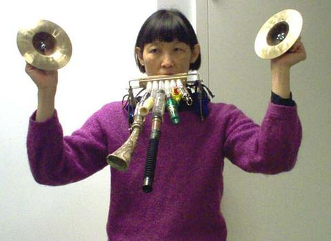 <strong>Pianist Margaret Leng Tan with an array of noisemakers strapped to her, 12/9/03.</strong>