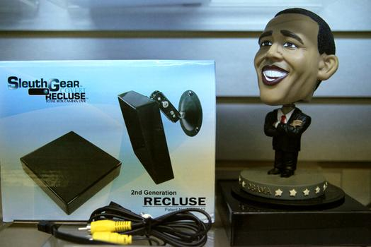 An Obama statuette standing on a platform with a hidden camera.