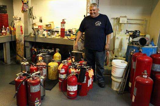 Peter Martinez Jr. with extinguishers at Master Fire Prevention.