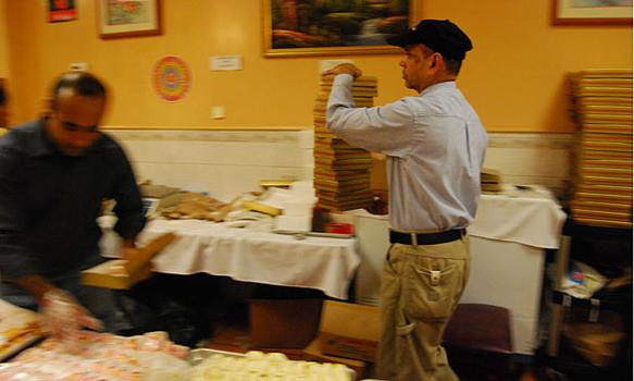 A worker carries an order of 14 pounds of sweets to a customer.